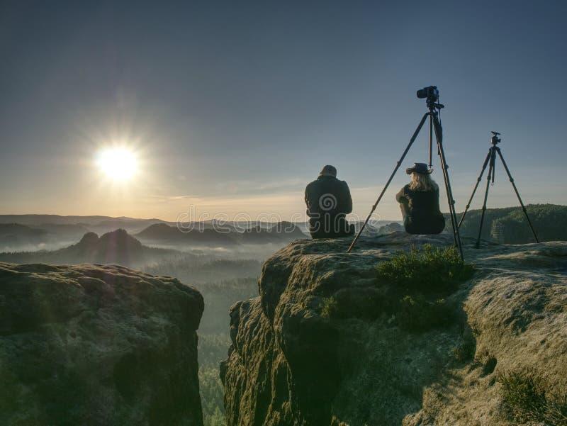 Os turistas dos pares tomam imagens ao fundo dos montes e do céu imagens de stock royalty free
