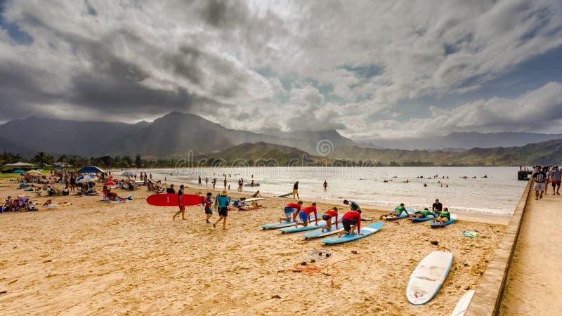 Os turistas e os locals apreciam igualmente a tarde morna na praia do Waioli da baía de Hanalei imagem de stock