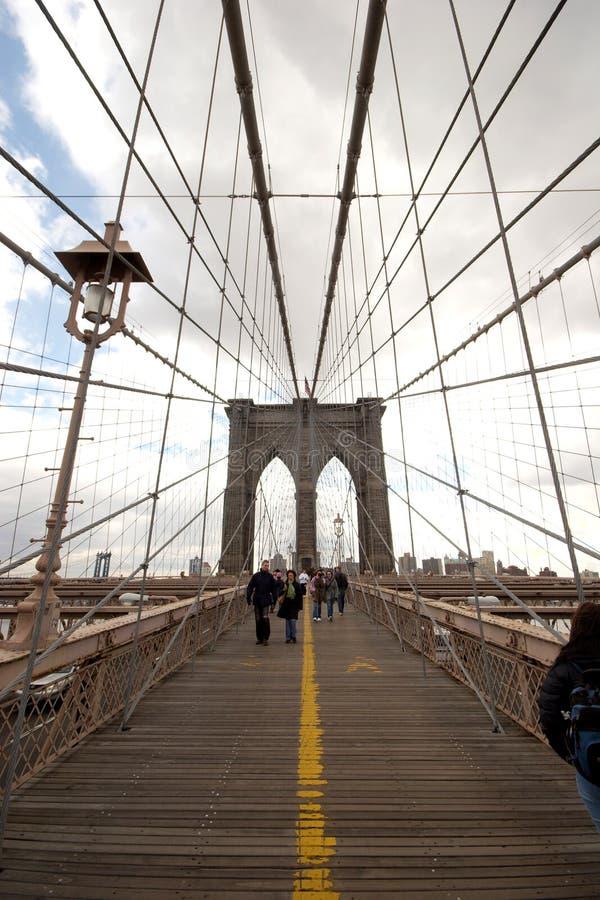 Os turistas e os assinantes andam ao longo da plataforma pedestre da ponte de Brooklyn, um mais baixo Manhattan imagem de stock royalty free