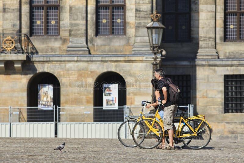 Os turistas em bicicletas alugado na represa de Amsterdão esquadram. fotos de stock