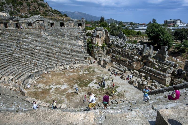 Os turistas escalam sobre as ruínas do teatro greco-romano no local antigo de Myra em Demre em Turquia imagem de stock