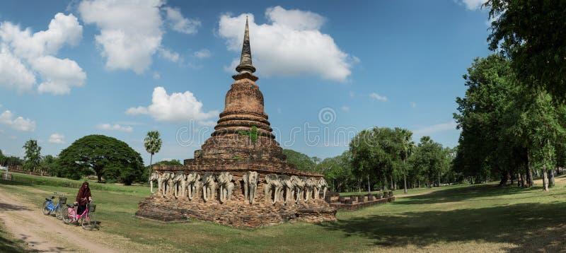 Os turistas estão explorando ruínas antigas, usando bicicletas alugadas tailândia fotos de stock royalty free