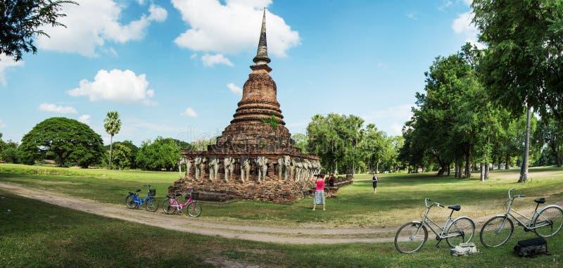 Os turistas exploram ruínas antigas, usando bicicletas alugadas tailândia imagens de stock