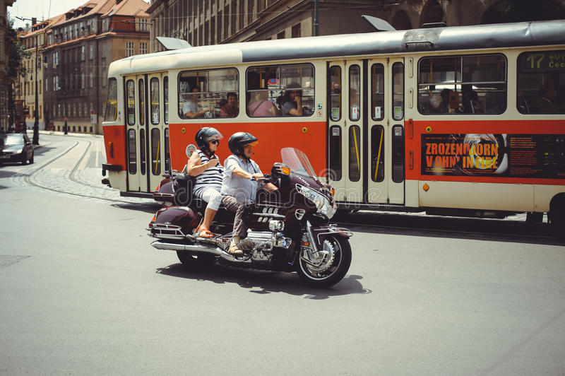 Os turistas idosos em uma motocicleta montam abaixo da rua em Praga fotos de stock