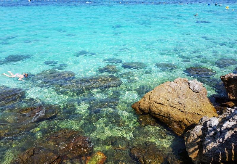 Os turistas mergulham na água de cristal de turquesa perto do recurso tropical foto de stock
