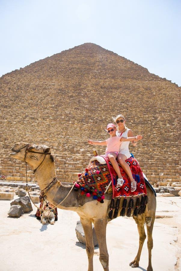 Os turistas mulher e menina estão montando um camelo no fundo das pirâmides em Egito fotografia de stock royalty free