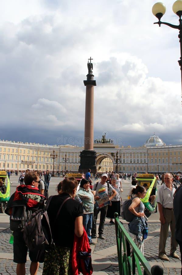 Os turistas no quadrado do palácio são oferecidos uma viagem ao longo dos canais de St Petersburg foto de stock royalty free