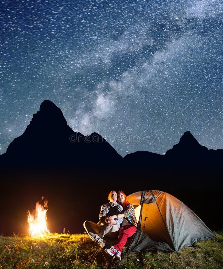 Os turistas novos dos pares que olham ao brilham o céu estrelado e a Via Látea no acampamento na noite perto da fogueira fotos de stock