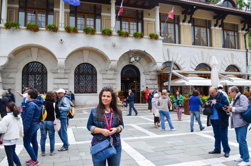 Os turistas perto da entrada da pedra calcária cavam em Postojna fotografia de stock royalty free