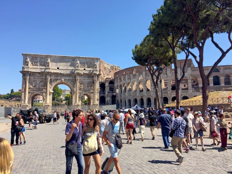 Os turistas perto de Colosseum e de Constantim arqueiam em Roma, Itália imagem de stock