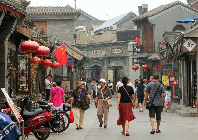 Os turistas que andam em Yandan conduzem o hutong, a rua antiga no Pequim imagens de stock