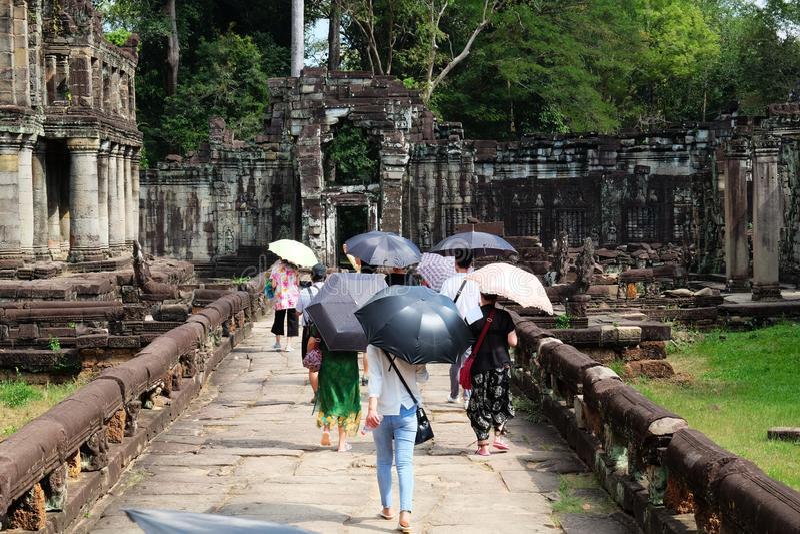 Os turistas que escondem sob guarda-chuvas veem as vistas Povos com guarda-chuvas Ru?nas medievais fotos de stock royalty free