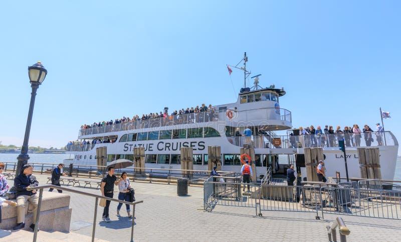 Os turistas que montam a estátua cruzam ferryboat no parque de bateria em um mais baixo Manhattan em NYC imagens de stock royalty free