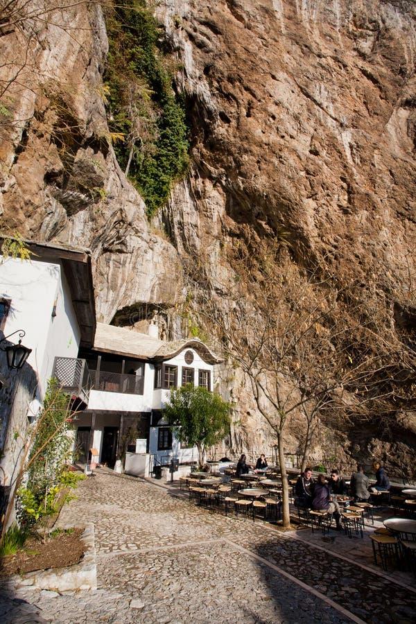 Os turistas relaxam no café exterior perto do monastério histórico Blagaj Tekke de Sufi nas montanhas fotografia de stock royalty free