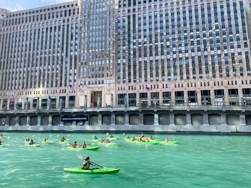 Os turistas remam nos caiaque no Chicago River na frente do mercado de mercadoria fotografia de stock