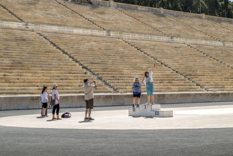 Os turistas são fotografados no pódio no estádio de Panathenaic foto de stock royalty free