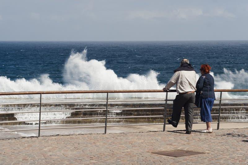 Os turistas superiores dos povos observam ondas esmagar em um cais foto de stock