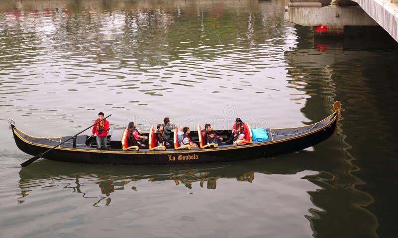 Os turistas tomam um passeio da gôndola no rio do amor imagem de stock royalty free