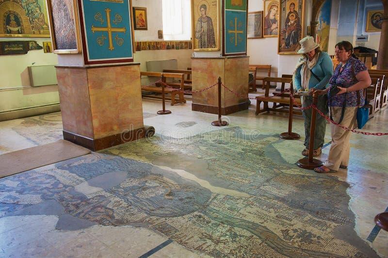 Os turistas visitam a basílica ortodoxo bizantina de St George com o mapa de mosaico da Terra Santa em Madaba, Jordânia fotografia de stock royalty free