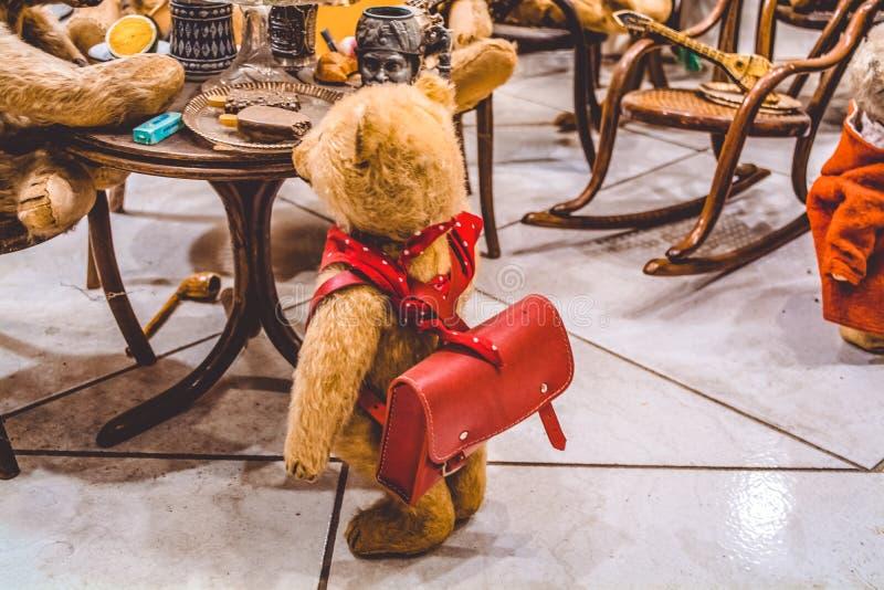 Os ursos marrons da peluche sentam-se em uma tabela e comem-se o gelado, e perto deles a criança com uma trouxa Exposição dos bri foto de stock