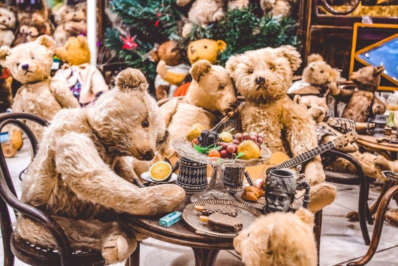 Os ursos marrons da peluche têm uma boa estadia e comem o gelado, jogam a guitarra Exposição dos brinquedos Partido em anos novos imagens de stock royalty free
