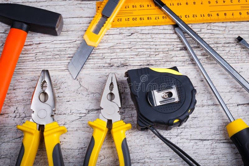 Os vários alicates, chaves de fenda, réguas, martelos e fita métrica Vista superior fotografia de stock