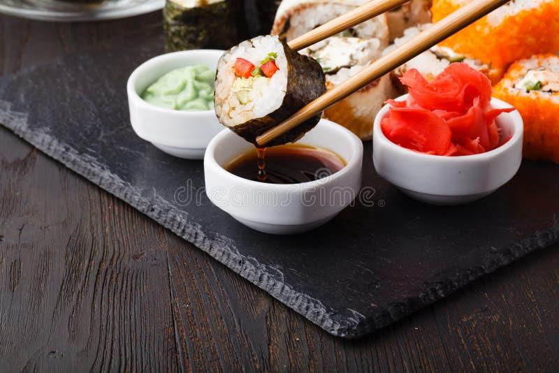 Os vários tipos do alimento do sushi serviram na pedra preta imagem de stock