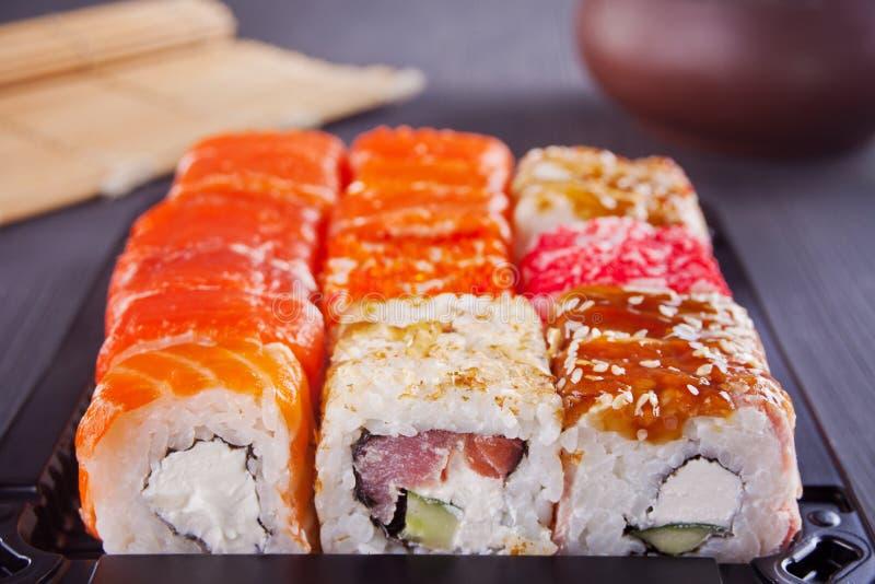 Os vários tipos do sushi serviram em uma tabela imagens de stock