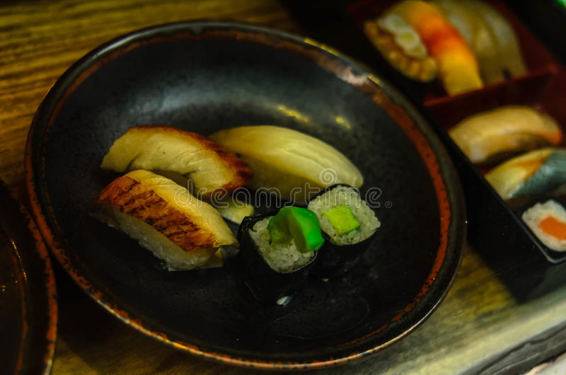Os vários tipos do sushi serviram na placa cermic marrom Sashimi do sushi e rolos de sushi ajustados fotos de stock royalty free