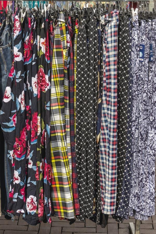 Os vários vestidos coloridos que penduram no roupa submetem fotografia de stock royalty free