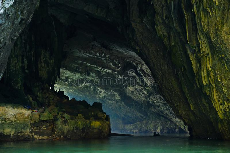 Os vagabundos sejam lagos/Vietname, 03/11/2017: Barco que passa no rio através da caverna gigante nos vagabundos vietnamianos do  imagem de stock