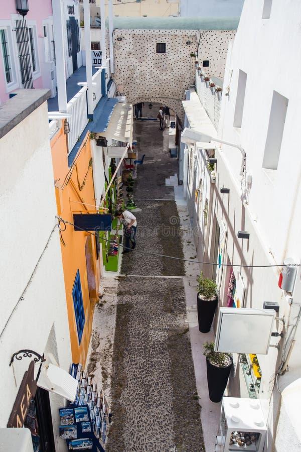 Os van de Gourgeousmening straat in witte ommuurde stad van Fira in Santorini, Griekenland, met winkels aan beide kanten stock afbeeldingen