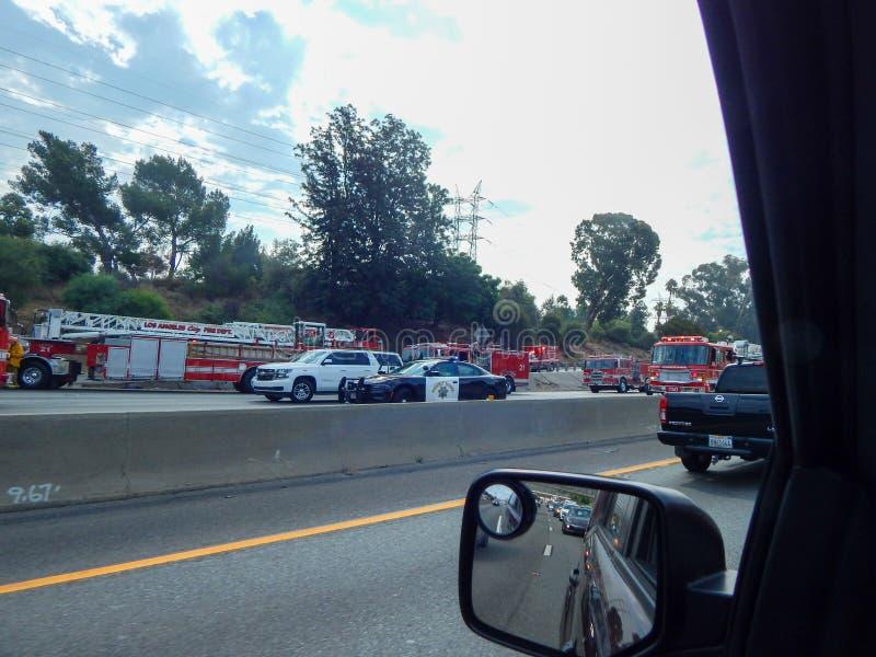 Os veículos de socorro alinham a autoestrada durante o acidente do caminhão virado na autoestrada 5 em Los Angeles imagem de stock