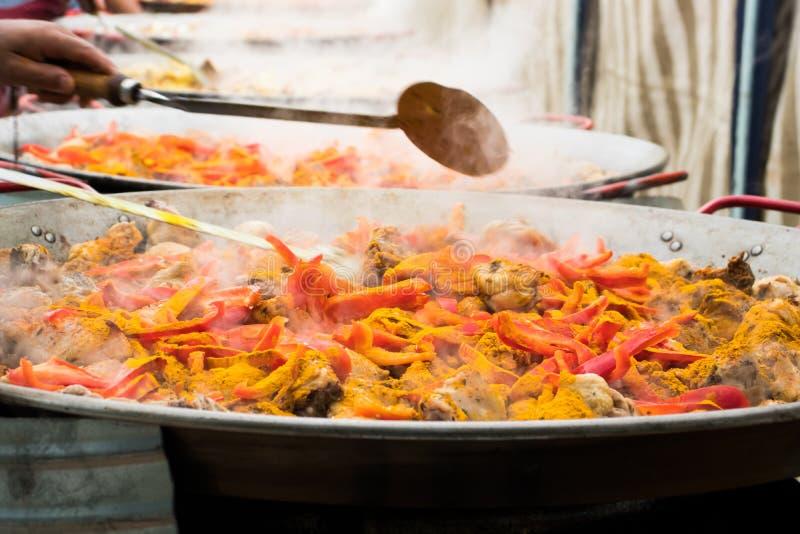 Os vegetais, as especiarias e a carne da galinha são cozinhados em umas bandejas gigantes para preparar um paella coletivo imagem de stock royalty free