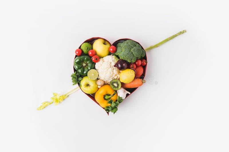 os vegetais e os frutos que colocam no coração deram forma ao prato imagem de stock