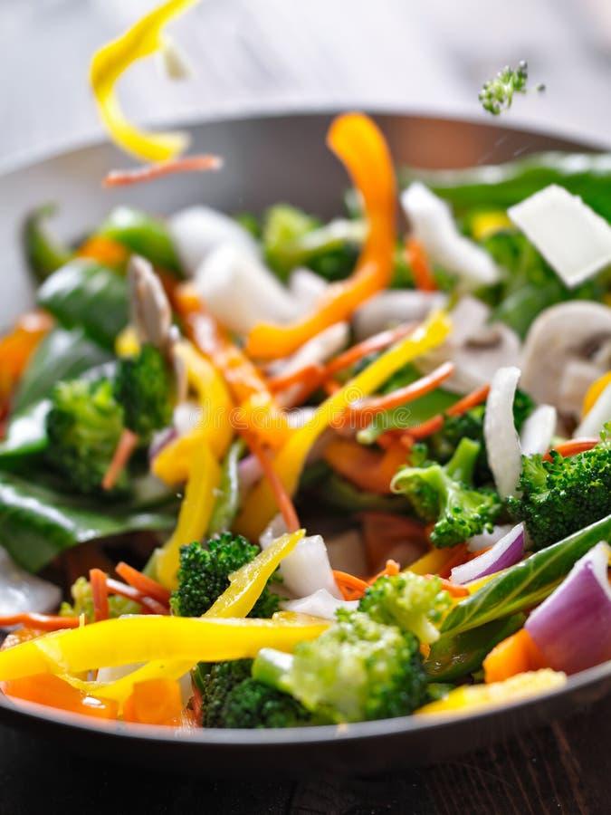 Os vegetais que caem em uma agitação fritam o frigideira chinesa. fotografia de stock