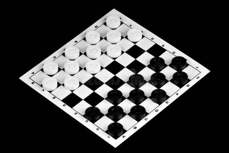 Os verificadores são um jogo antagônico da lógica antiga popular da placa com partes preto e branco especiais, em uma placa da pi fotos de stock