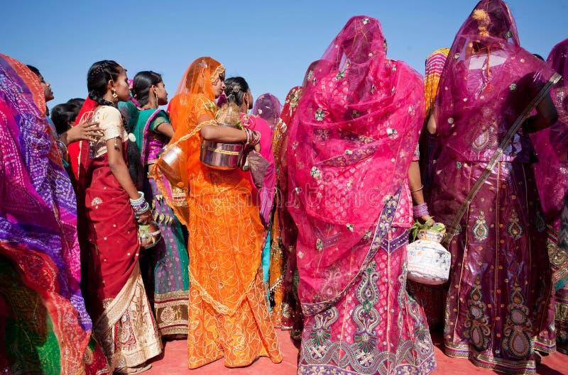 Os vestidos brilhantes das mulheres na vila abandonam o festival fotografia de stock royalty free