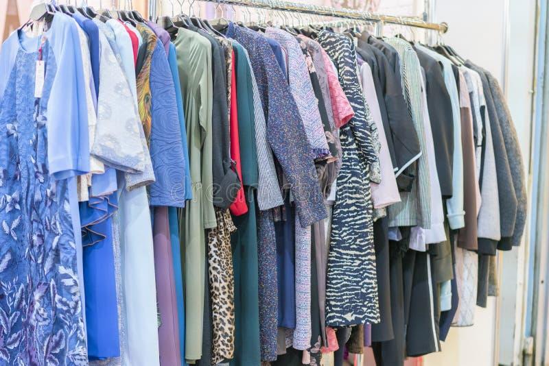 Os vestidos das mulheres coloridas em ganchos em uma loja varejo Conceito da forma e da compra Gancho com roupa na loja imagens de stock royalty free