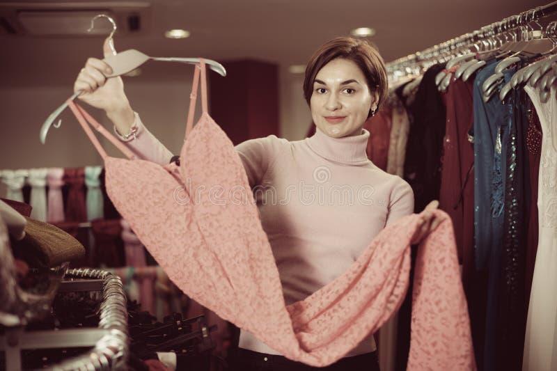 Os vestidos de exame do cliente fêmea em panos dos women's compram imagem de stock