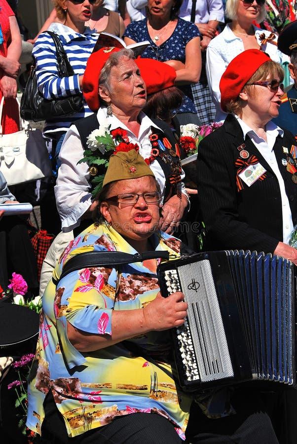 Os veteranos de guerra cantam músicas Uma mulher joga o acordeão fotografia de stock royalty free