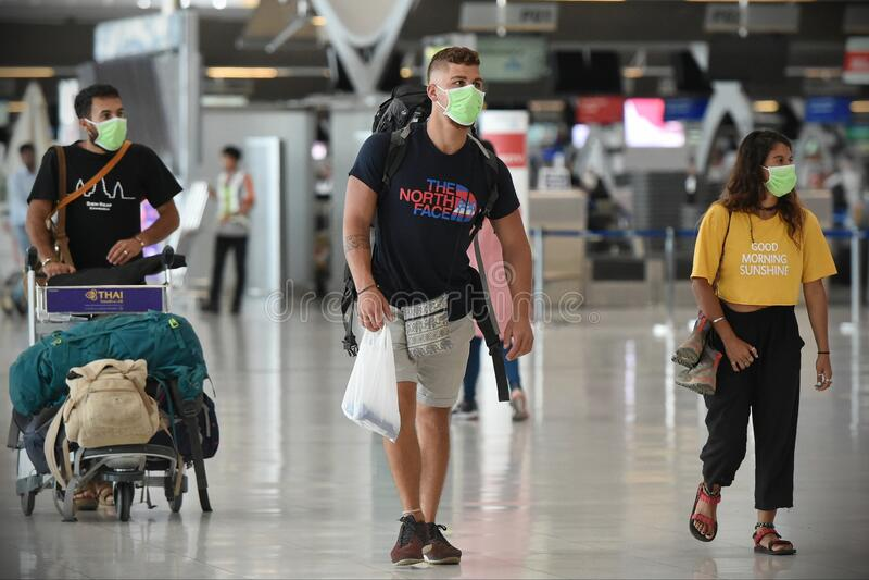 Os viajantes aéreos usam máscaras como precaução contra o código 19 causado pelo coronavírus imagens de stock royalty free