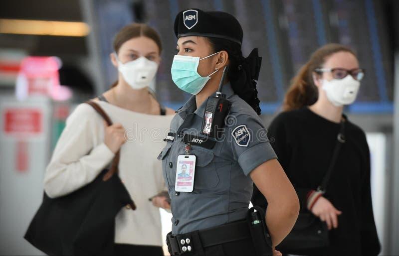 Os viajantes aéreos usam máscaras como precaução contra o código 19 causado pelo coronavírus foto de stock