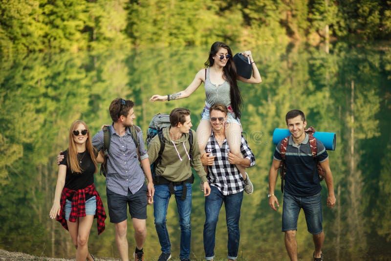Os viajantes alegres escutarem a música quando caminhada indo imagem de stock