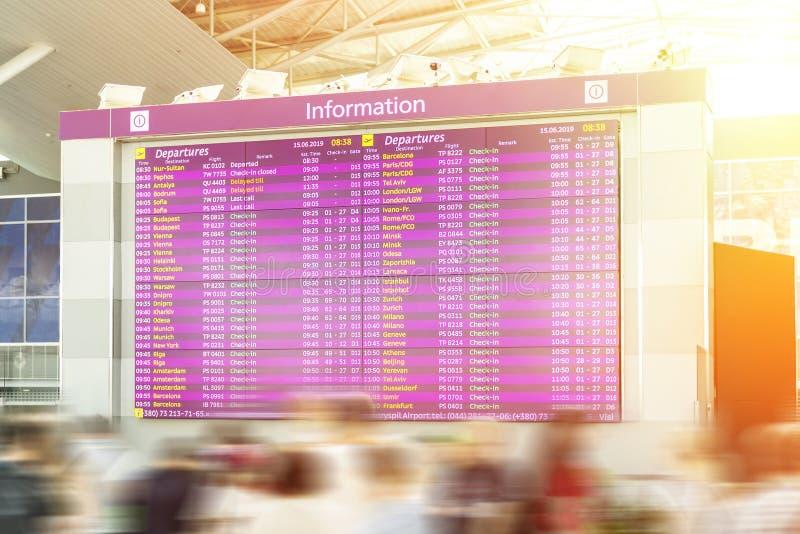 Os viajantes borrados movimento aglomeram-se olhando o feparture do fligh e o calendário de chegada no terminal de aeroporto Conc foto de stock royalty free