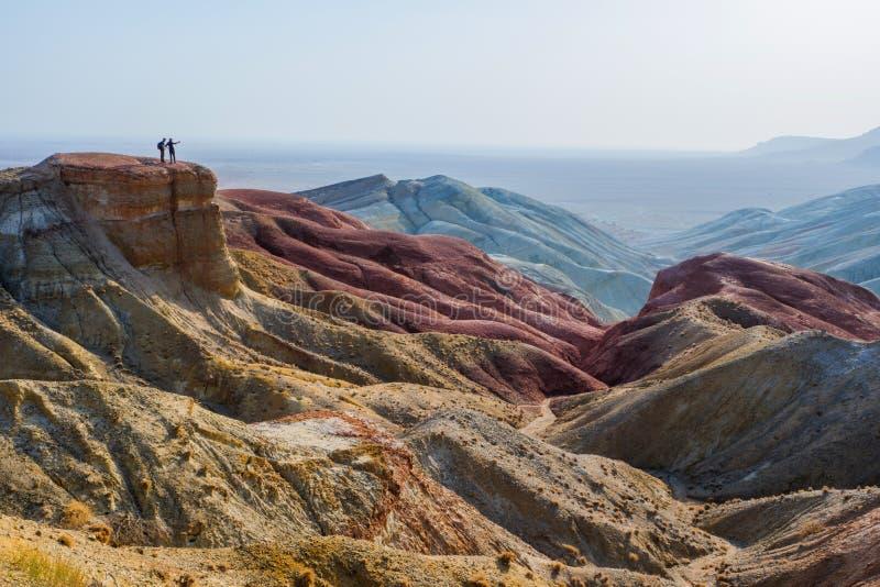 Os viajantes est?o na borda de um penhasco contra o contexto de uma paisagem ?pico da montanha do deserto fotos de stock