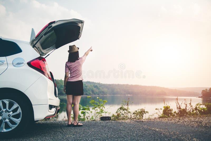 Os viajantes f?meas viajam com os carros no meio da natureza calma, viagem dos turistas para encontrar somente a beleza da nature fotos de stock