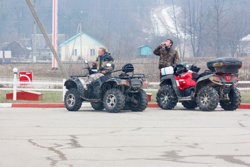 Os viajantes no quadrilátero bikes o café quente do resto e da bebida no campo no inverno imagens de stock