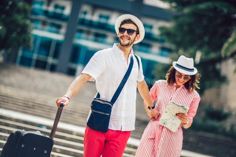Os viajantes novos acoplam o mapa da cidade da leitura e hotel da procura fotografia de stock