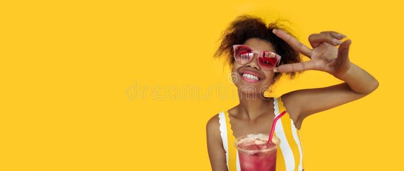 Os vidros africanos novos felizes do desgaste da bebida da posse da mulher riem o olhar na câmera imagens de stock royalty free
